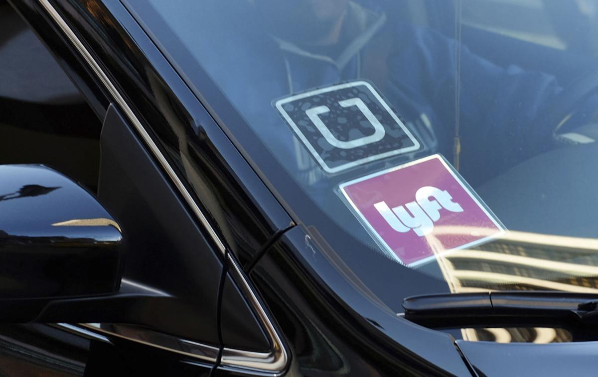 FILE - In this Jan. 12, 2016, file photo, a ride share car displays Lyft and Uber stickers on its front windshield in downtown Los Angeles. Law enforcement agencies and ride-hailing companies are intensifying efforts to warn passengers against getting in without checking to ensure both the vehicle and driver are legitimate.  AP Photo/Richard Vogel, File