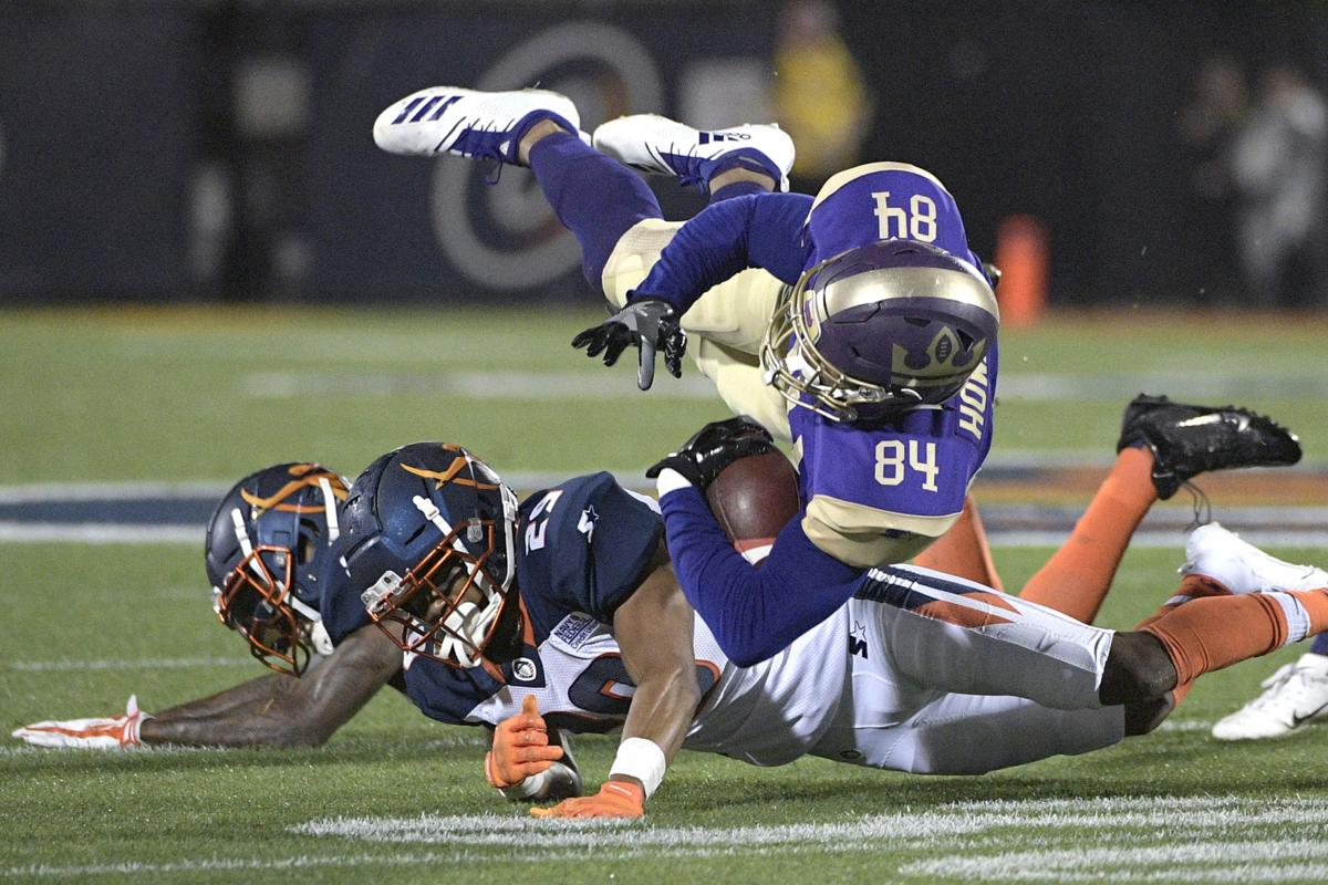 FILE - In this Feb. 9, 2019, file photo, Atlanta Legends receiver Bug Howard (84) is tackled by Orlando Apollos safety Will Hill and defensive back Keith Reaser (29) after catching a pass during the first half of an Alliance of American Football game, in Orlando, Fla.  AP Photo/Phelan M. Ebenhack
