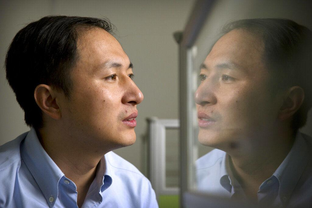 FILE - In this Oct. 10, 2018, file photo, He Jiankui is reflected in a glass panel as he works at a computer at a laboratory in Shenzhen in southern China's Guangdong province. A Chinese investigation says Chinese scientist He, behind the reported birth of two babies whose genes had been edited in hopes of making them resistant to the AIDS virus, acted on his own and will be punished for any violations of the law.  AP Photo/Mark Schiefelbein, File