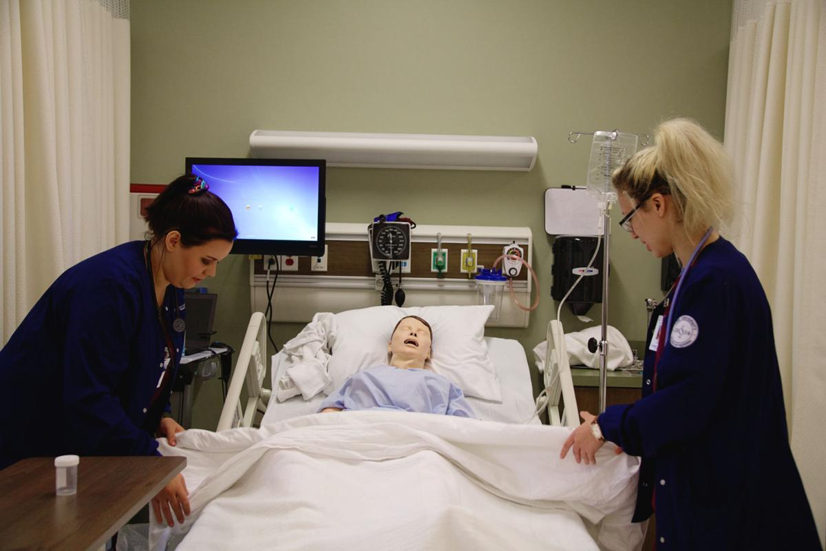 Sophomore nursing students demonstrate proper patient care.  Photo by John David Clark