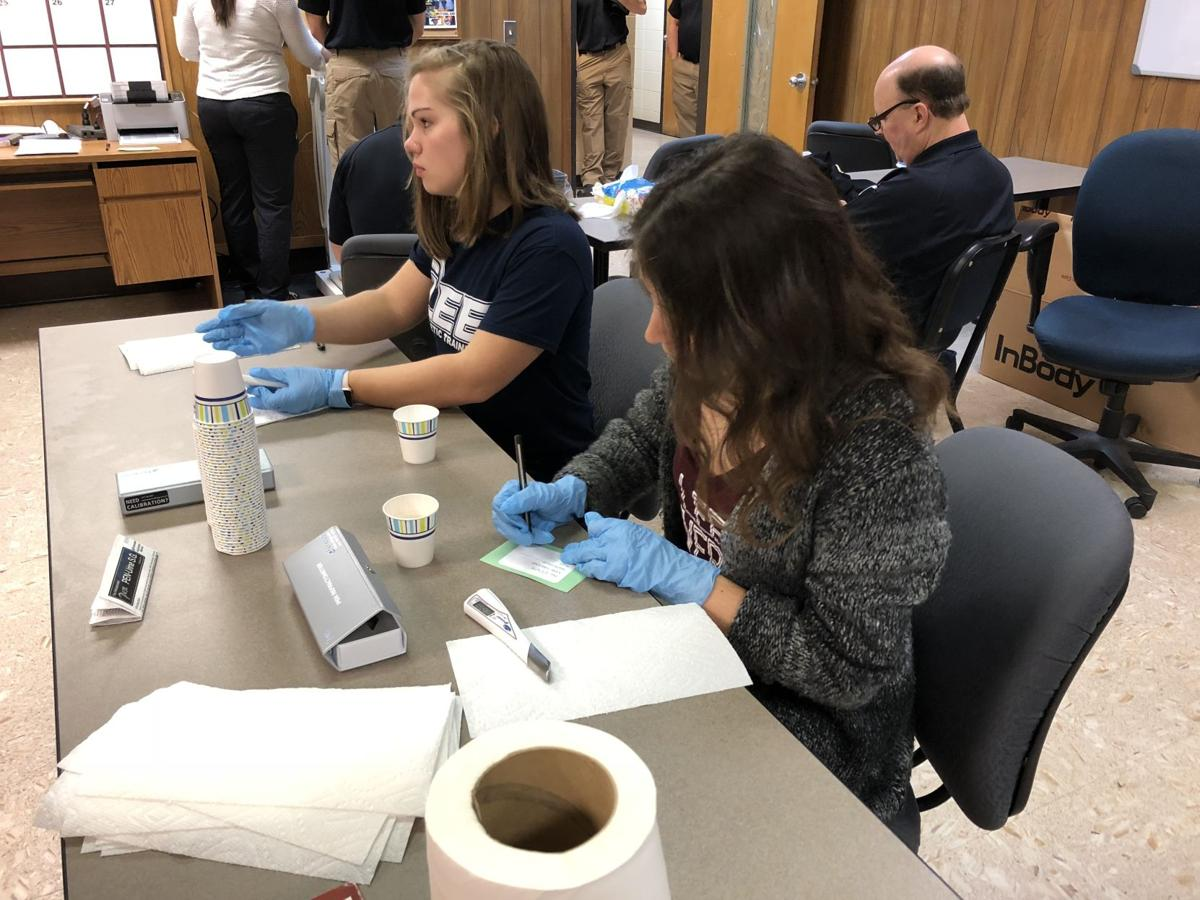 Three Exercise Science students (two pictured above) recorded firefighters' measurements and took a urine sample to see how they measure before and after injuries.  Courtesy of Aniston Morris