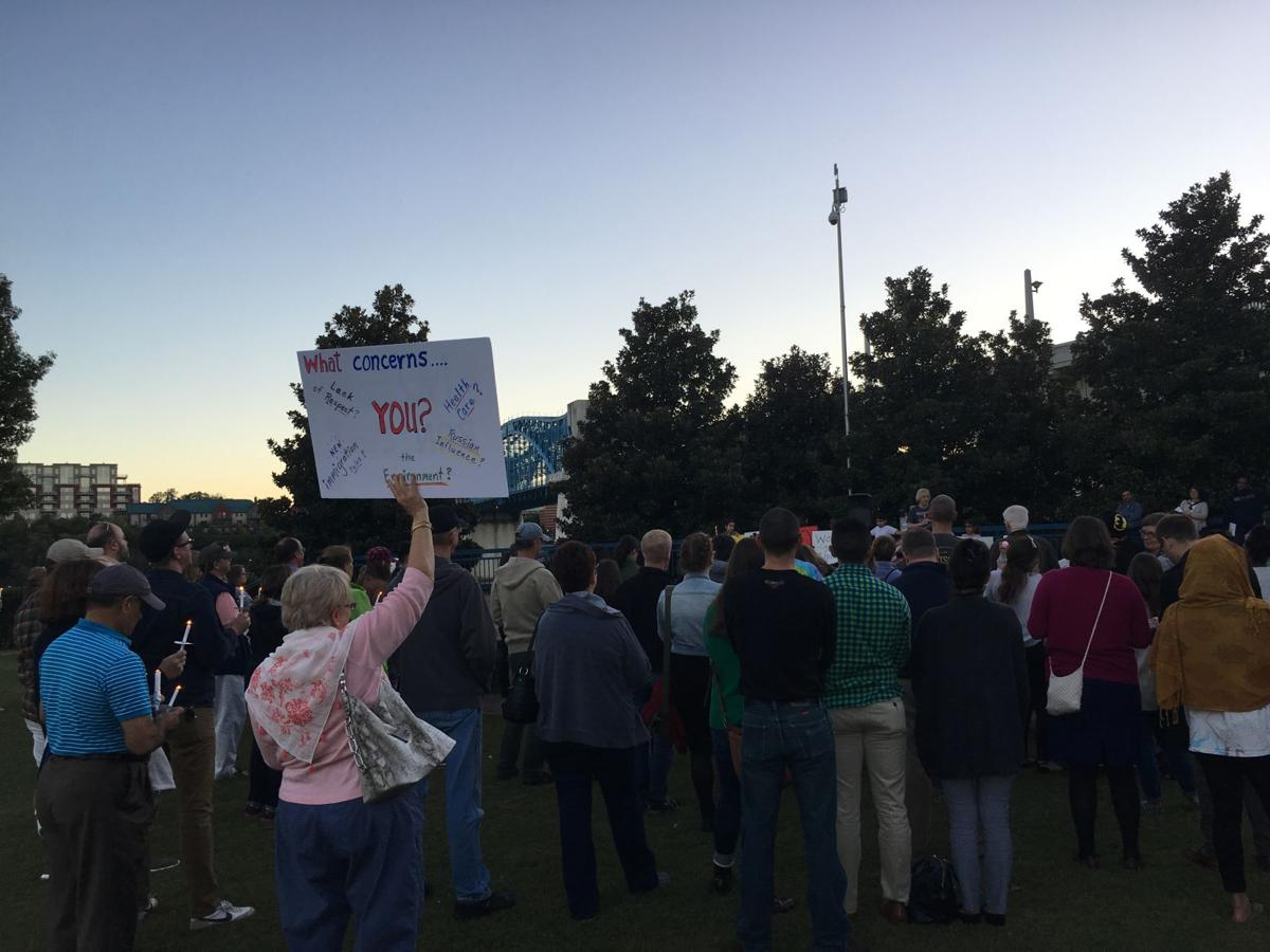Attendees hold signs at the candlelight vigil in Chattanooga's Coolidge Park.  Courtesy of Karina Radionova