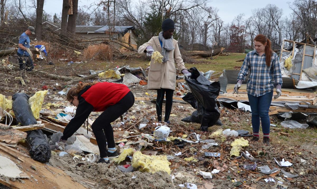 Students (from left) Amelia Wilson, Yinka Adedayo and Cassidy Gray help clean up tornado debris on Saturday, Dec. 3.