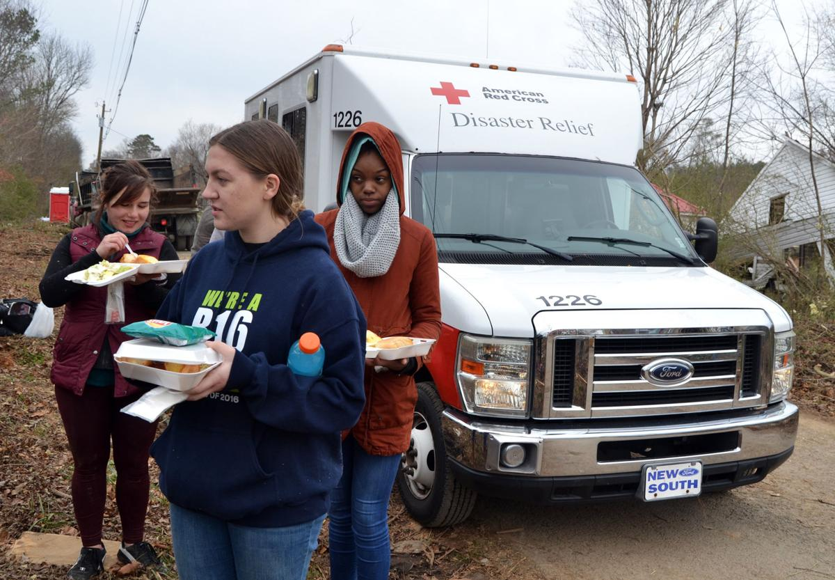 Lee students (from left) Anna Kholod, Addison Anton and Tamerra Fleming receive hot meals from the American Red Cross disaster relief team in Polk County, TN on Saturday, Dec. 3.