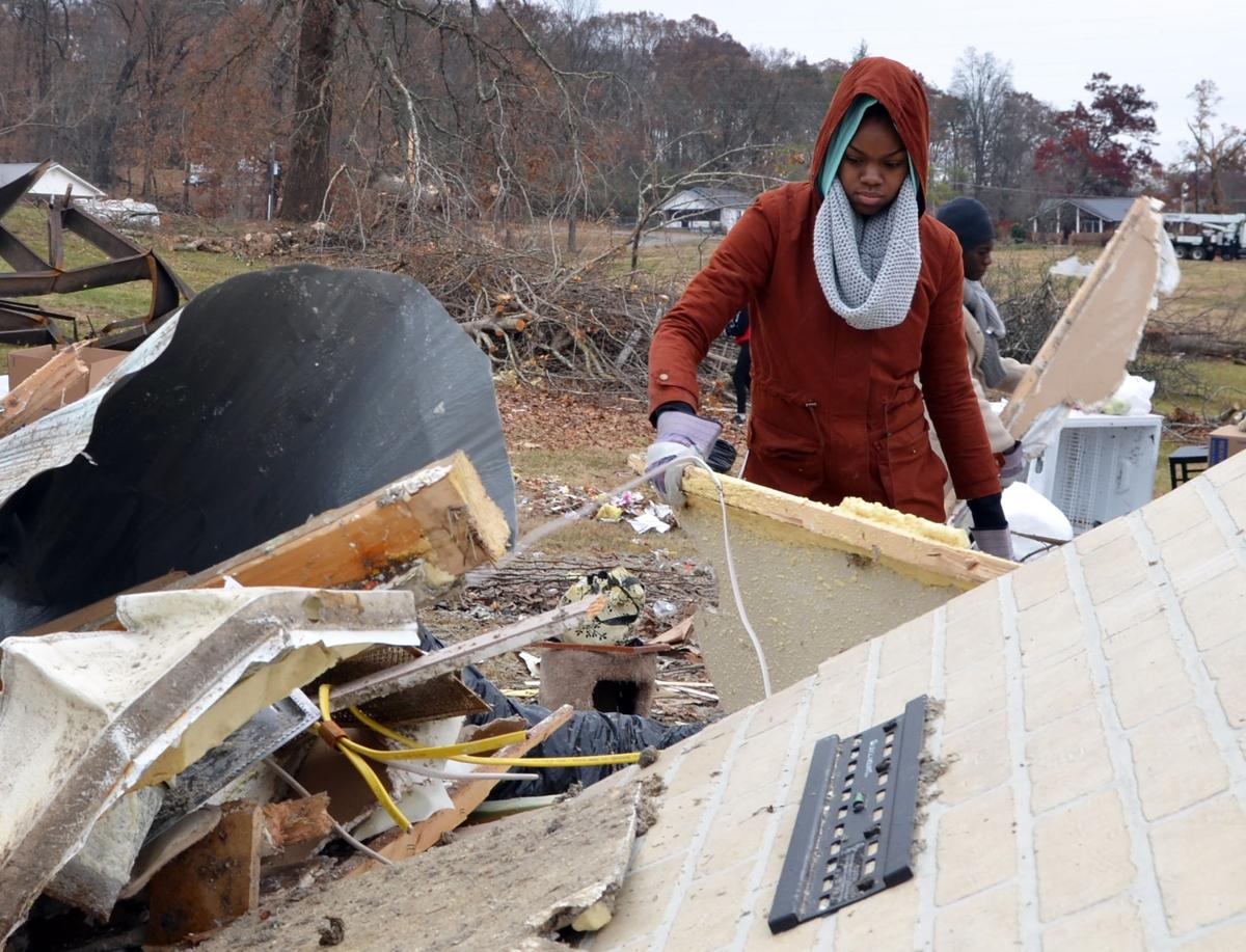 Tamerra Fleming moves debris from a pile on a site of tornado devastation in Polk County, TN on Saturday, Dec. 3.
