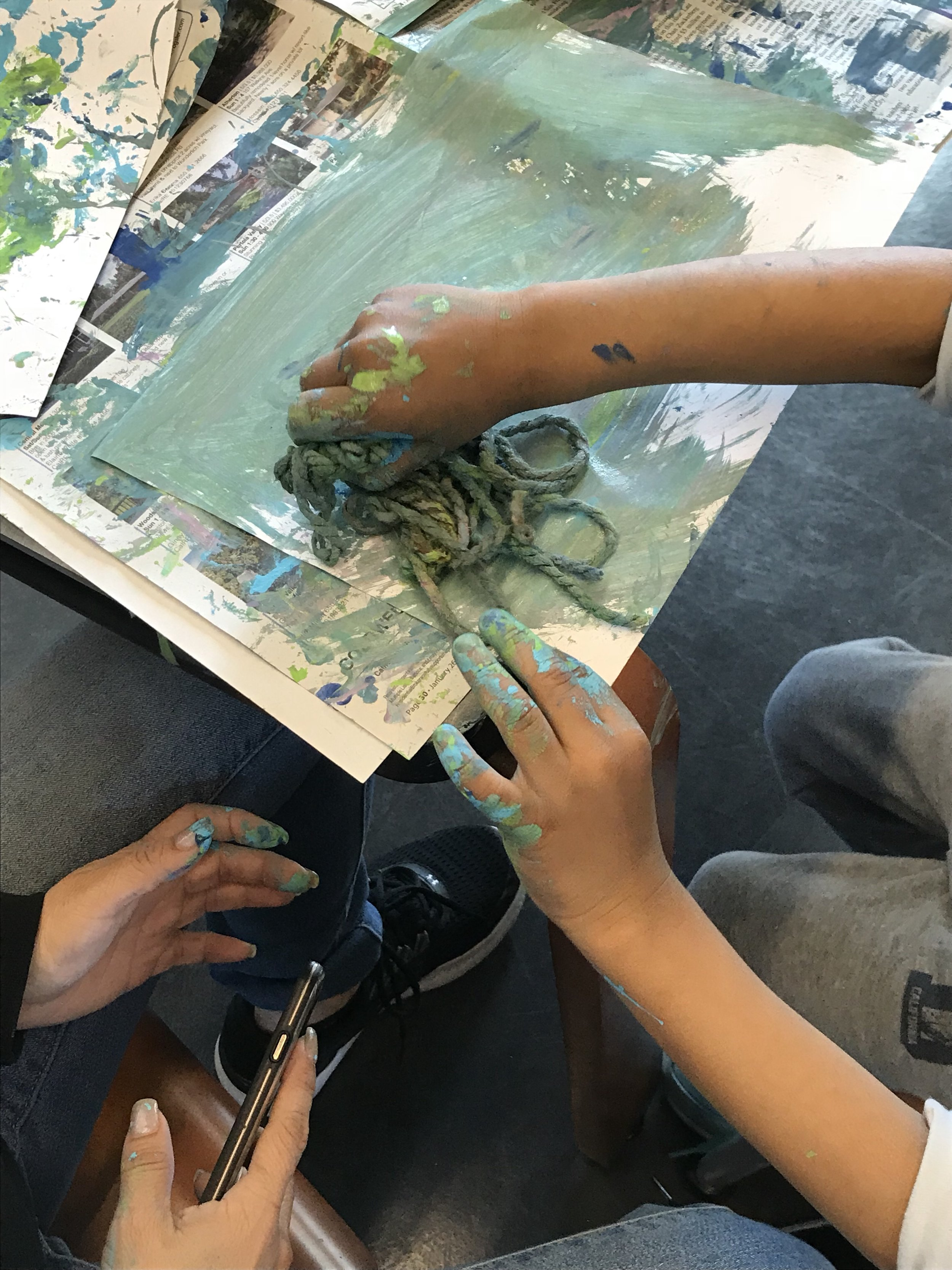 Here, the student is using his yarn in a pile to paint big swaths of color.