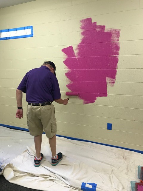 Rotary member paints a wall with purple paint.