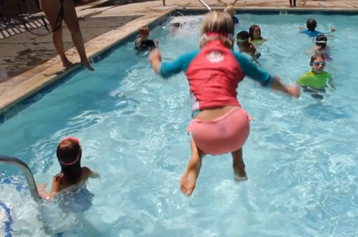 """This little girl is jumping off the Summerkids pool deck into 3 feet of water and about a foot away from the steps and railing. A """"counselor-lifeguard"""" watches her without doing anything. The American Red Cross (ARC) prohibits this activity, especially in water under 5 feet deep."""