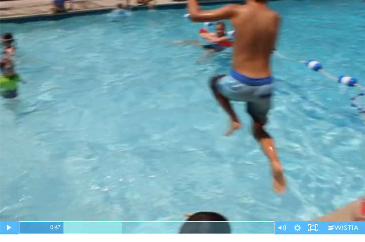 This little boy jumps off the pool deck into three feet of water, which is prohibited by the American Red Cross. The ARC prohibits running and jumping off of a pool deck.
