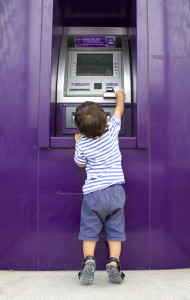 Little Boy Getting Money From An ATM