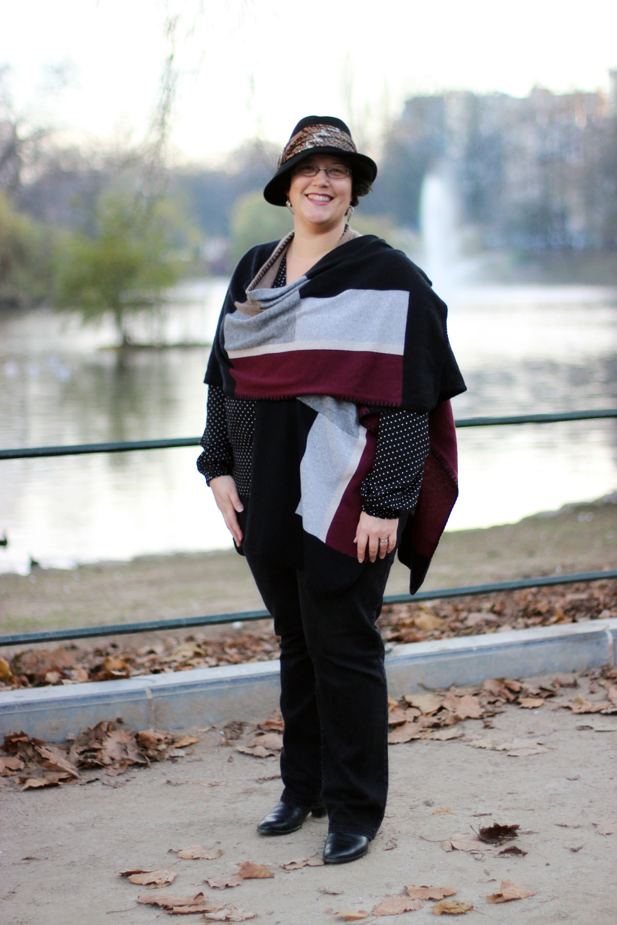 Sheila wearing a hat, shawl and black trousers.