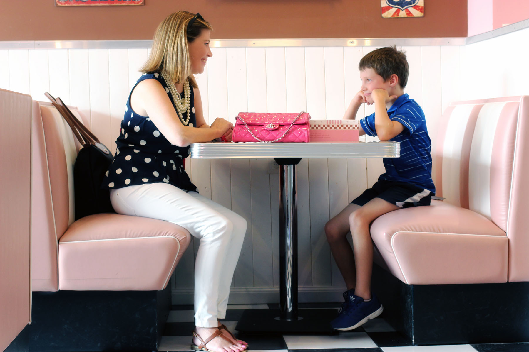 Wendy wearing preppy style clothes that make her feel confidence, sitting in a diner booth with her son.