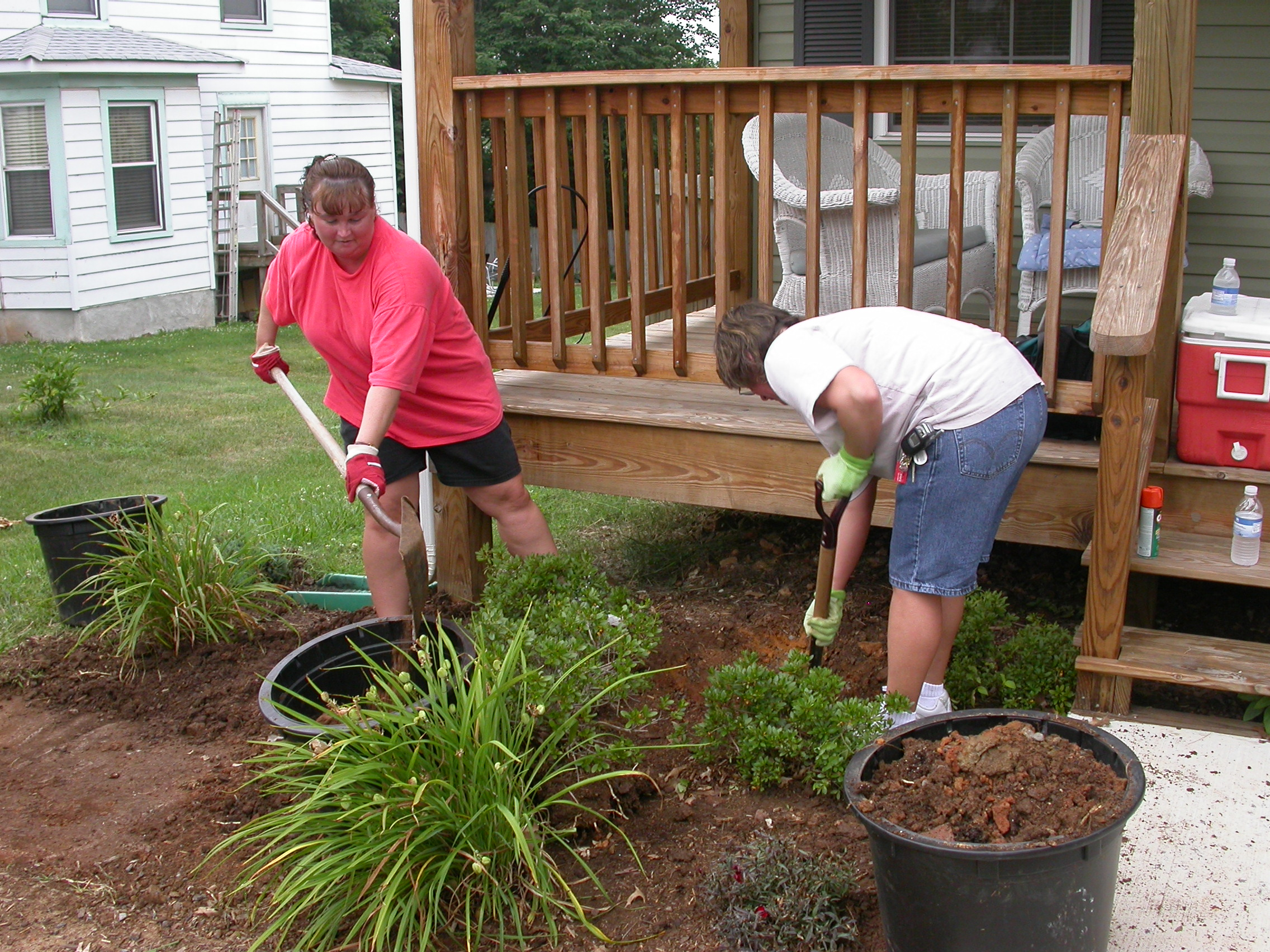 Two volunteers planting bushes in front of a Rush Homes property's front porch.