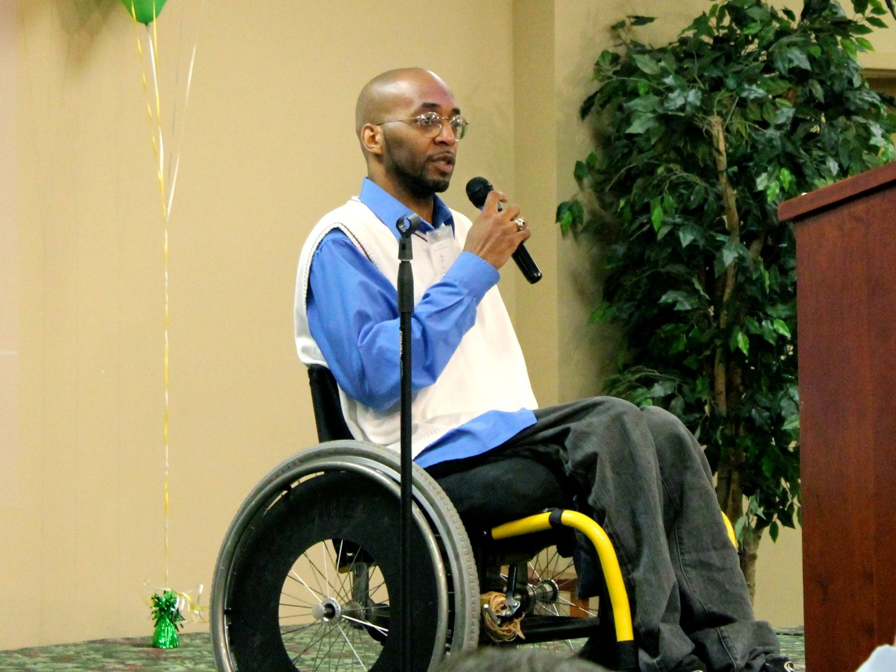 A Rush Home Tenant, in a wheel chair, speaks about the impact of the organization has had in his life in front of a crowd.