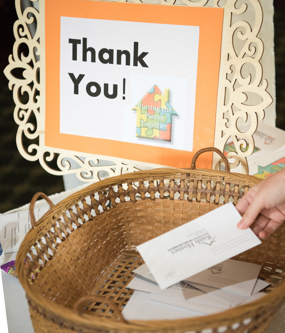A hand is dropping a donation envelope into a basket in a thank you sign next to it.