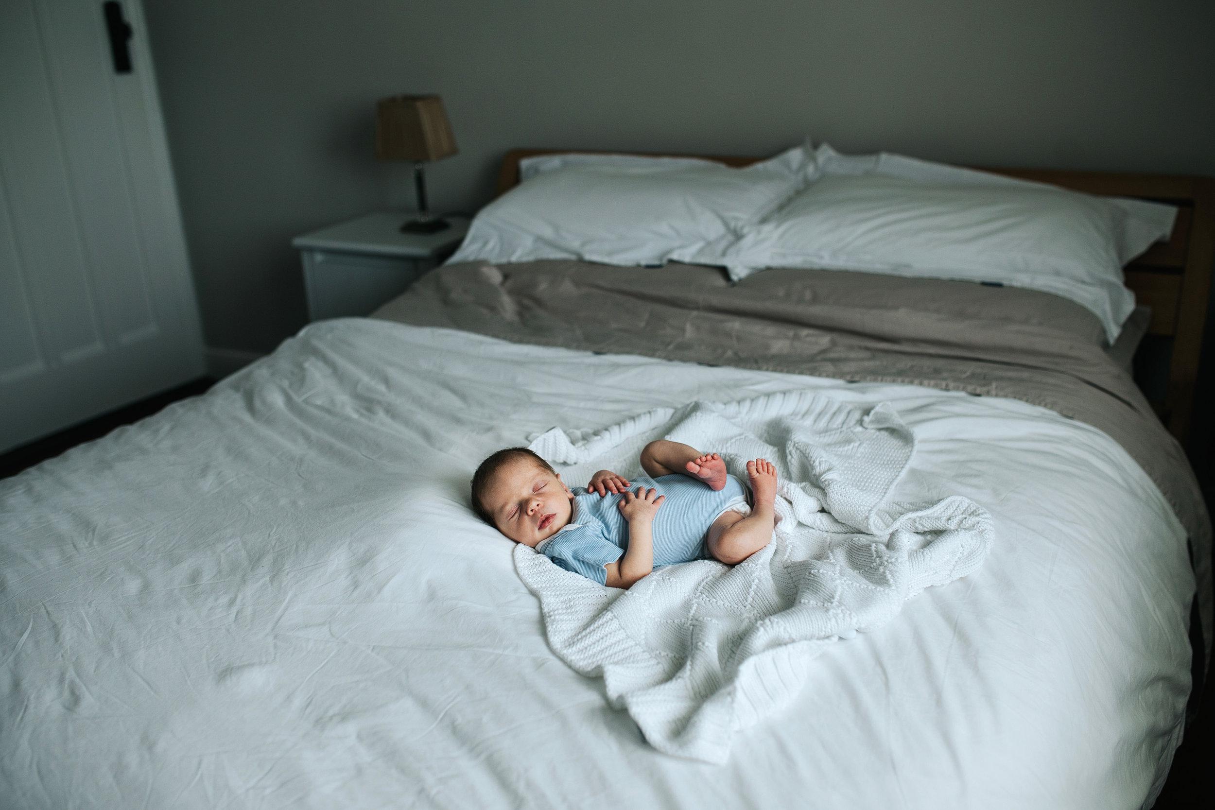 Newborn baby asleep on his parents bed
