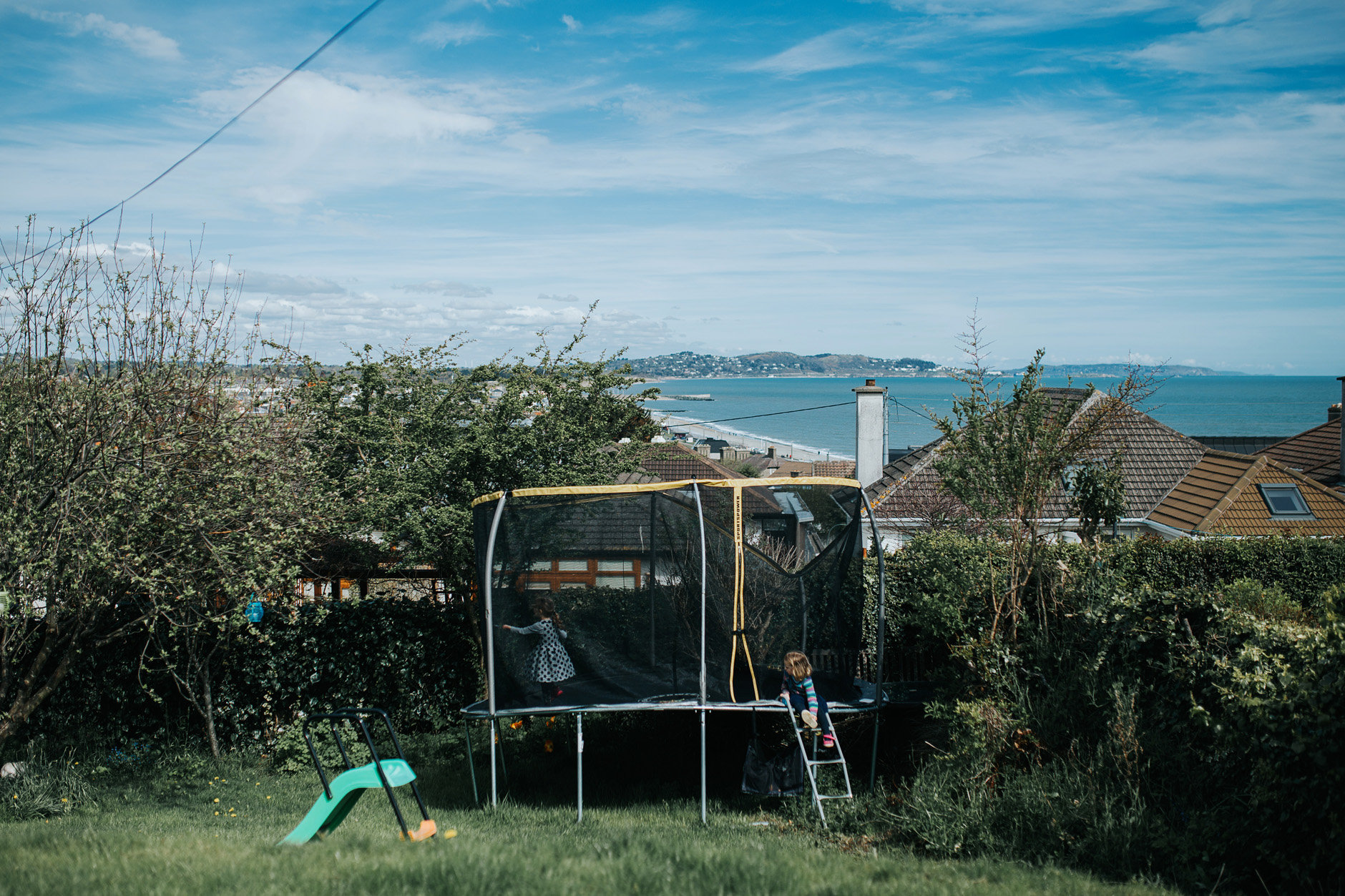 View of the sea, the garden and the trampoline with two girls on it