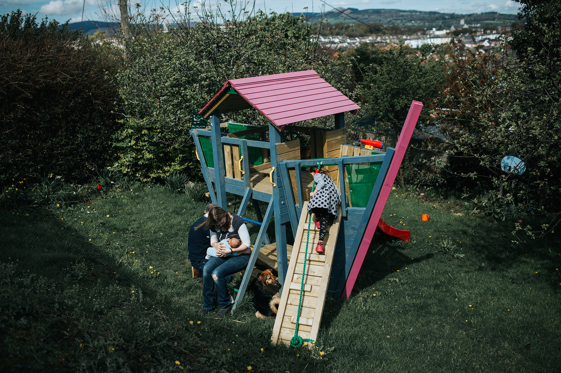View of the back garden playhouse in the shape of a boat. Children playing, dog and mother breastfeeding
