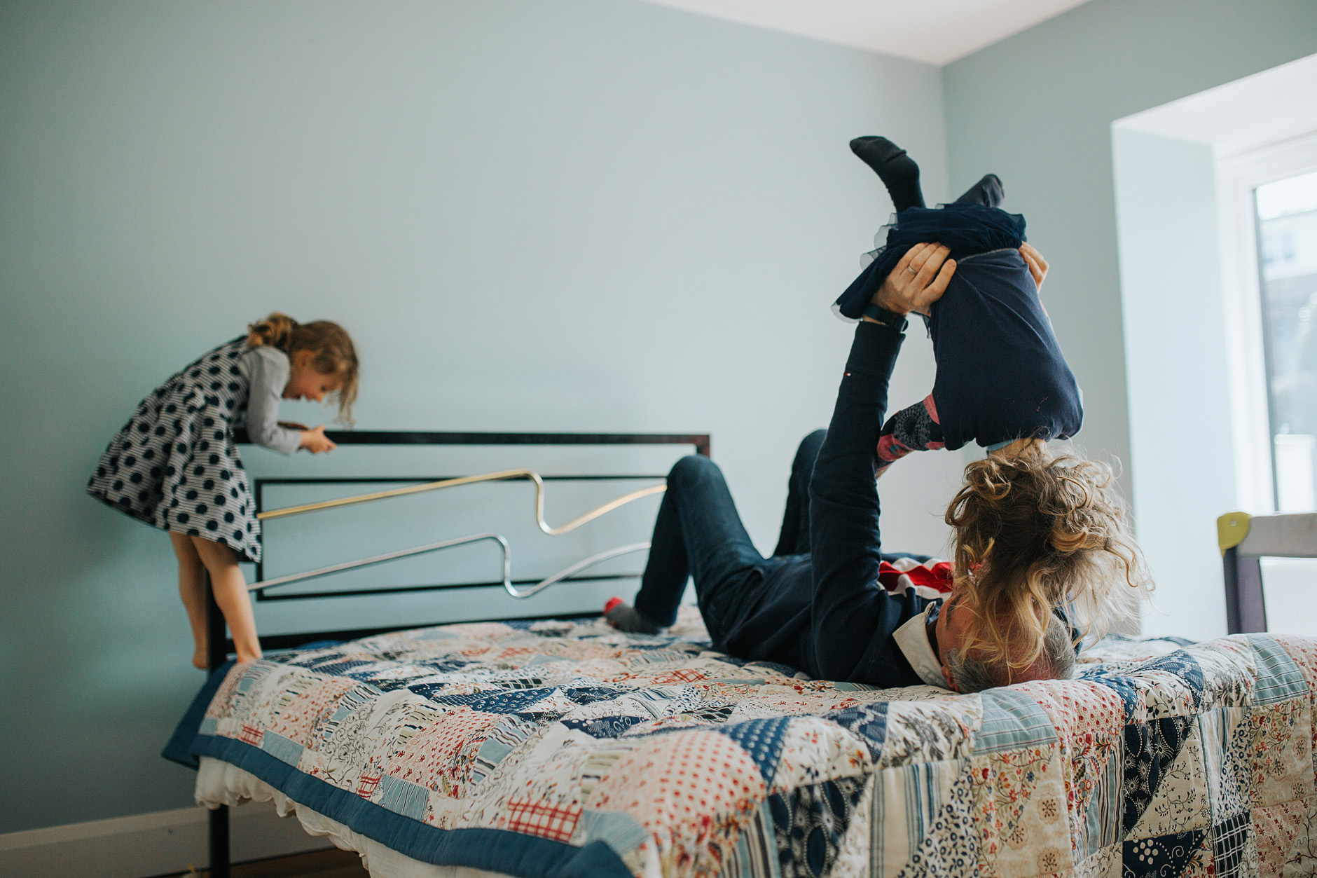 Father playing with the two daughters on the bed