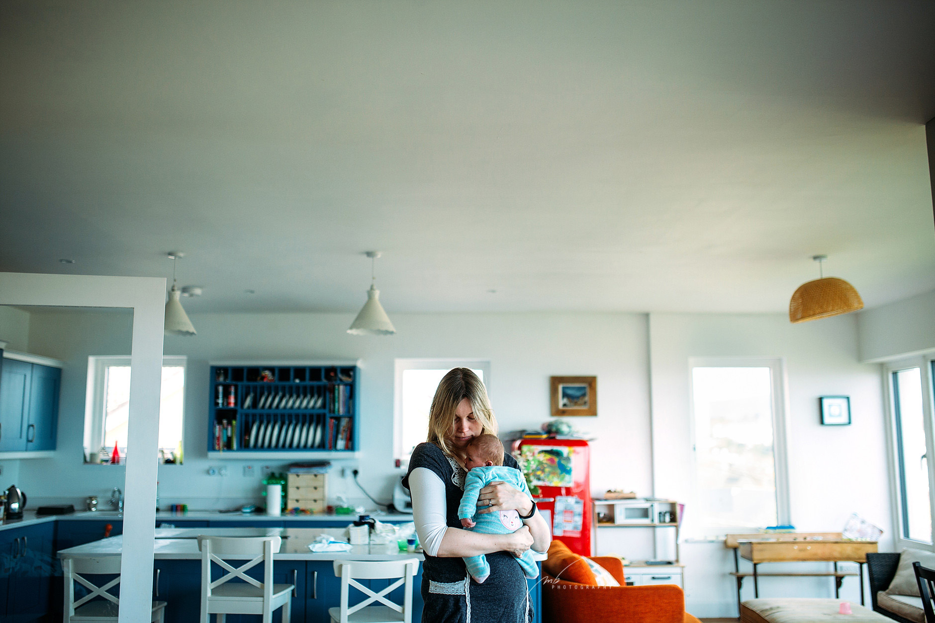 Mother holding & hugging her new baby in the middle of the kitchen