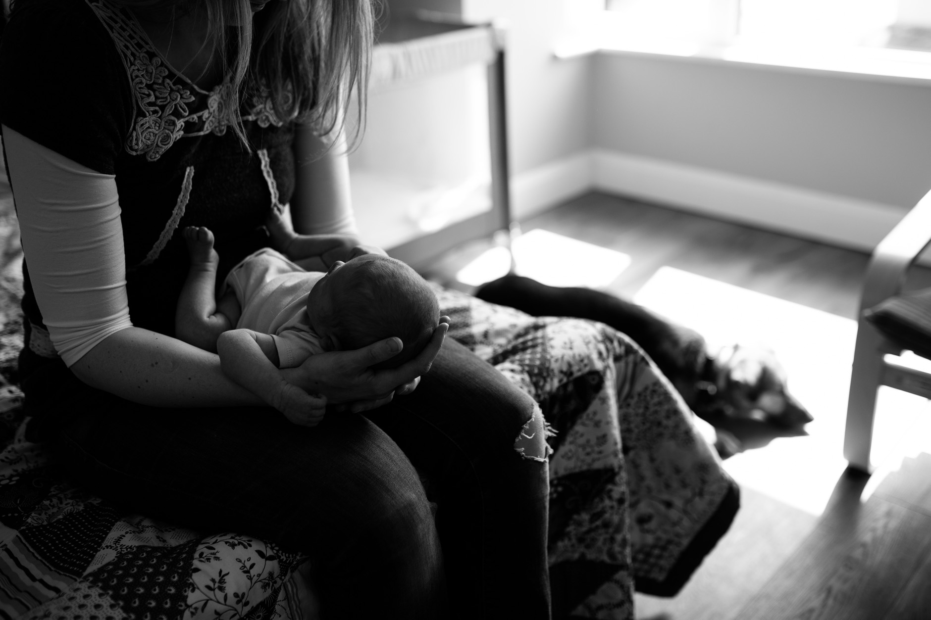 Mother holding her new baby on her knees.