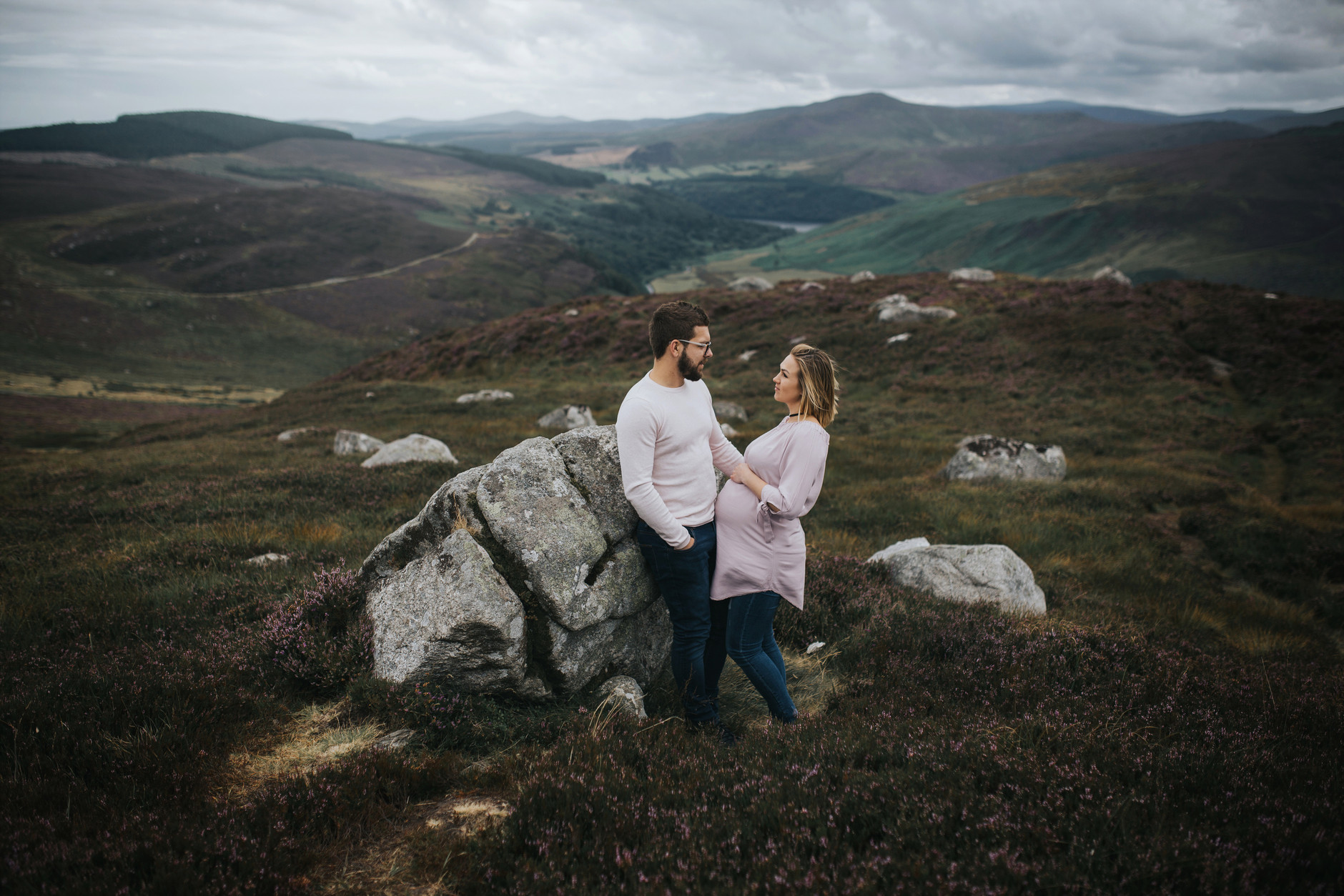 Expecting couple looking at each other in front of an amazing dublin mountains landscape