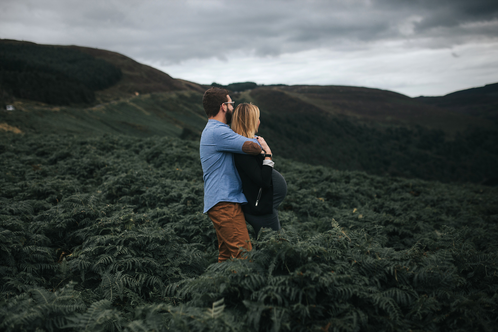 Husband hugging his pregnant wife while looking at the beautiful green irish landscape
