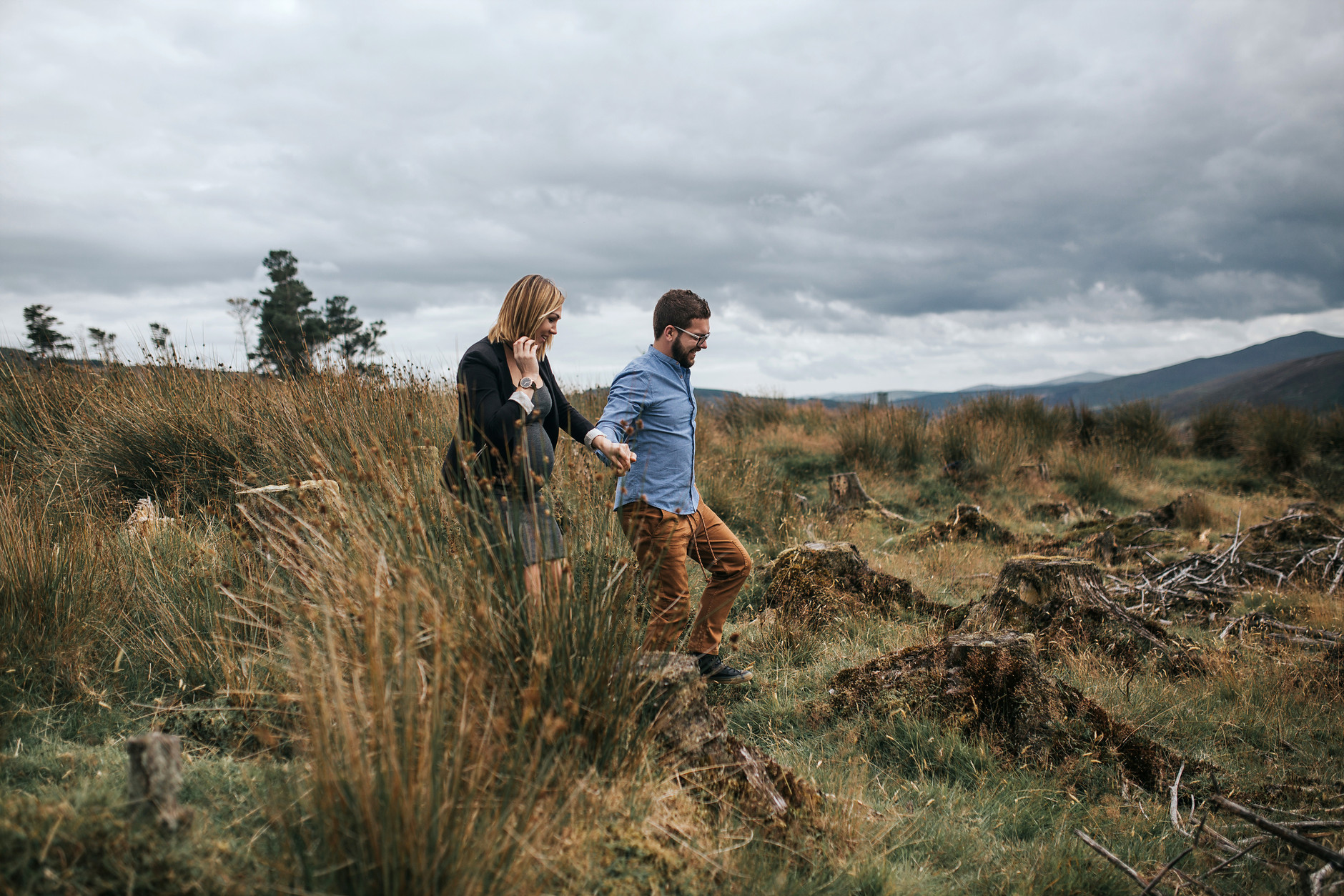 Couple holding hands and laughing while walking in the grass in Dublin mountains