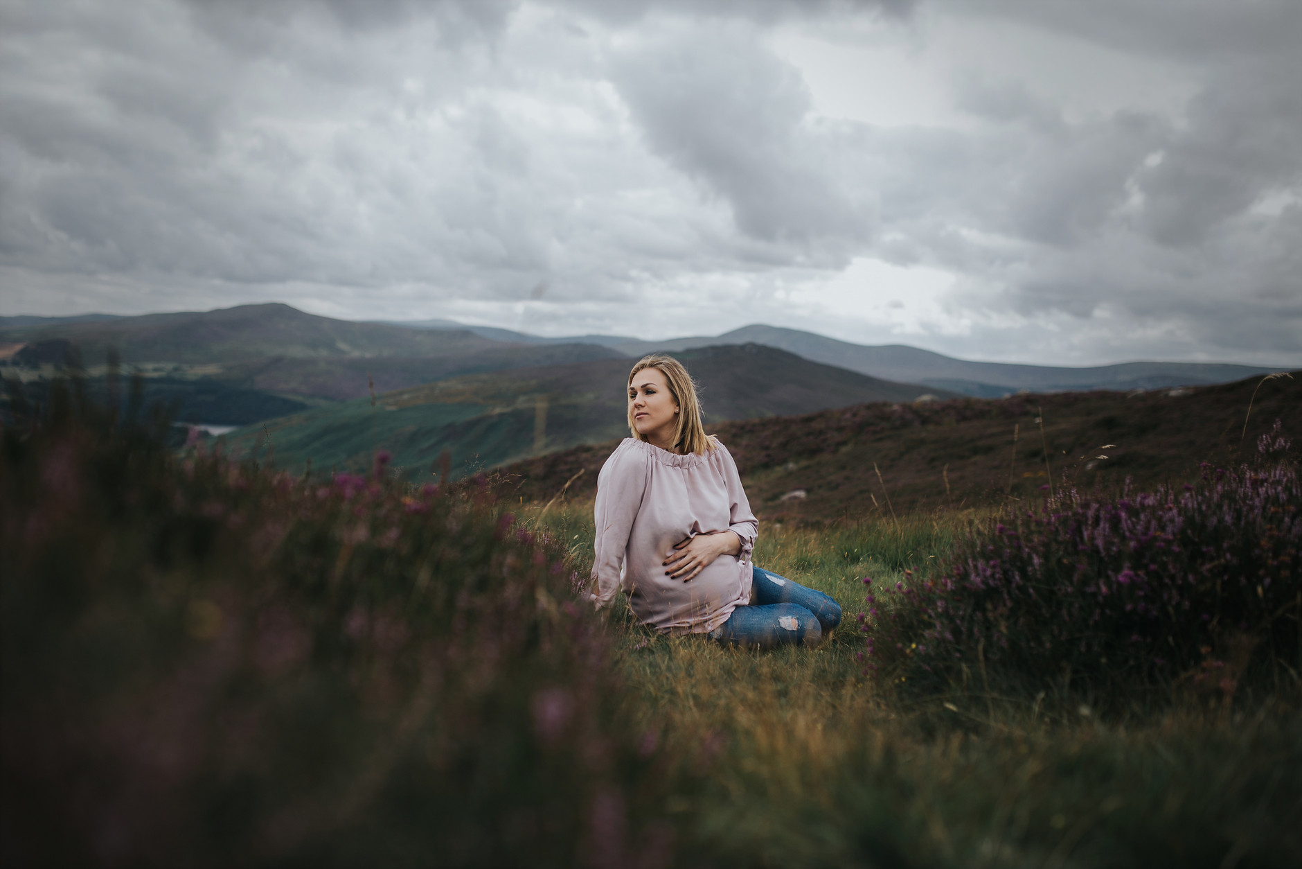 Pregnant mother sitting on the group in front of mountains and touching her belly