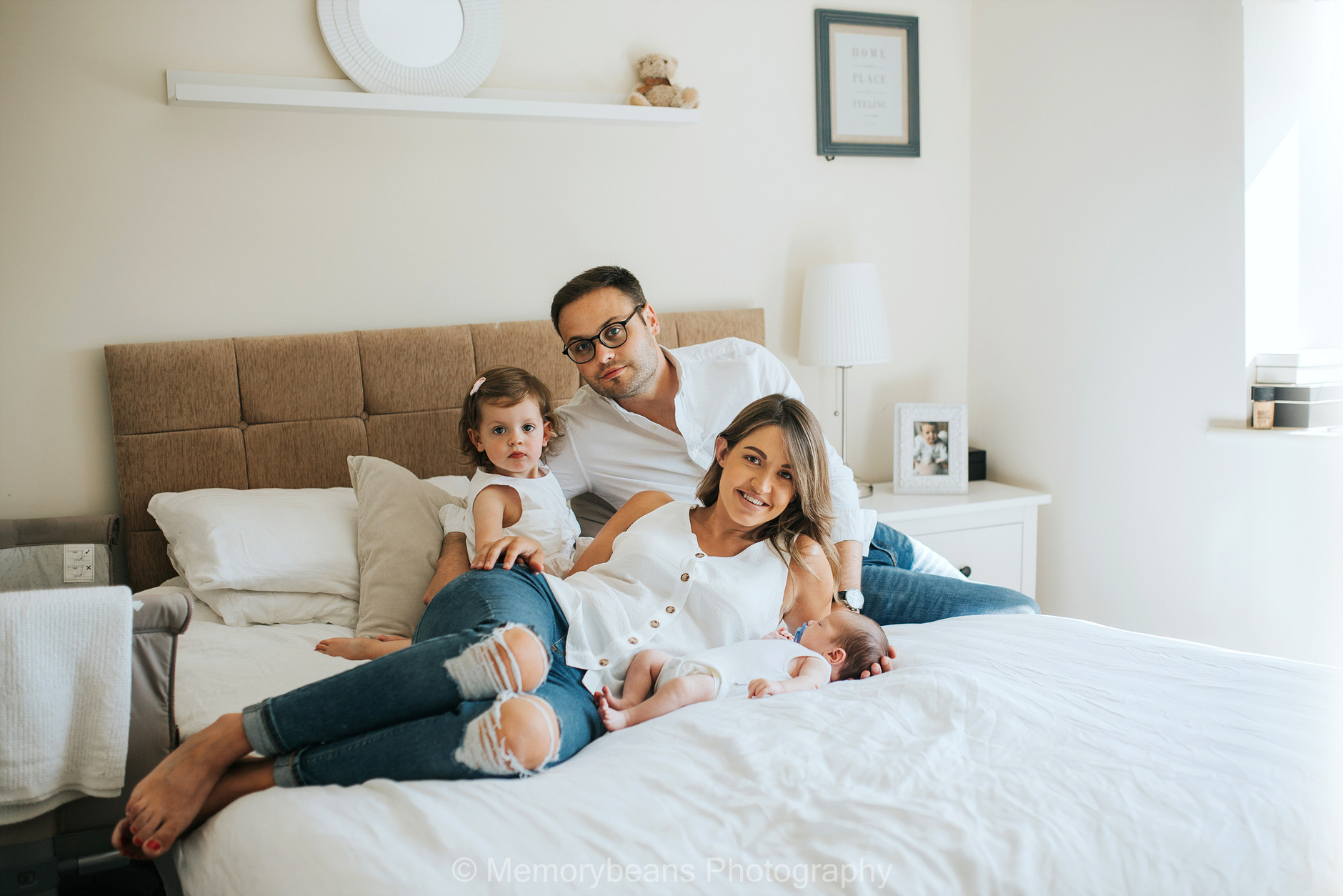 Whole family portrait with infant baby and sibling on the parents bed