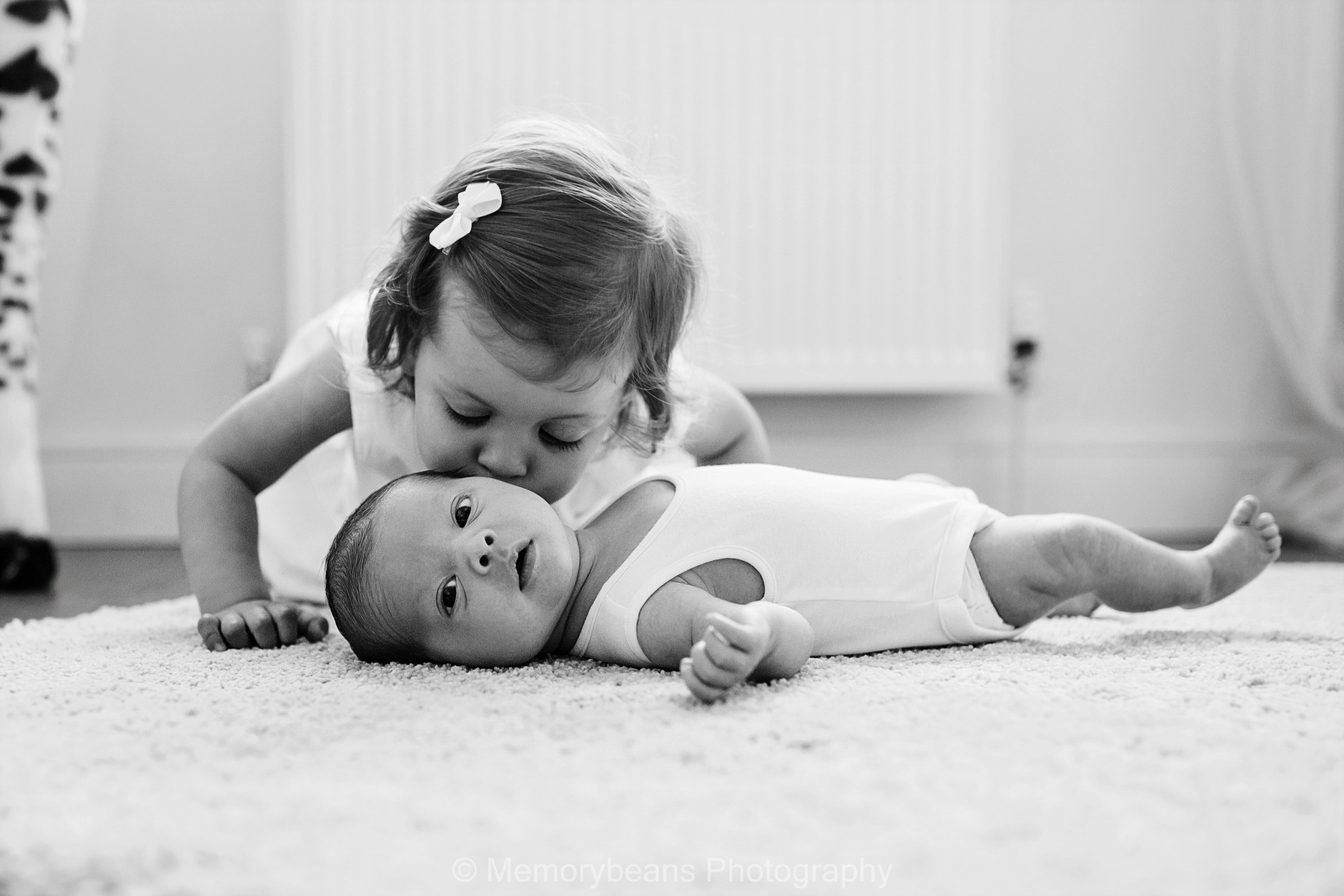 Newborn baby brother kissed by his big sister on the cheek