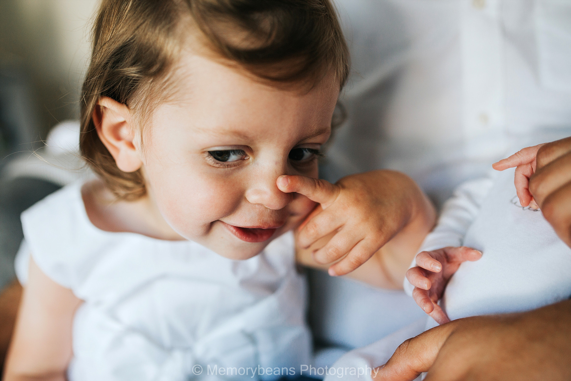 Toddler touching her nose and smiling