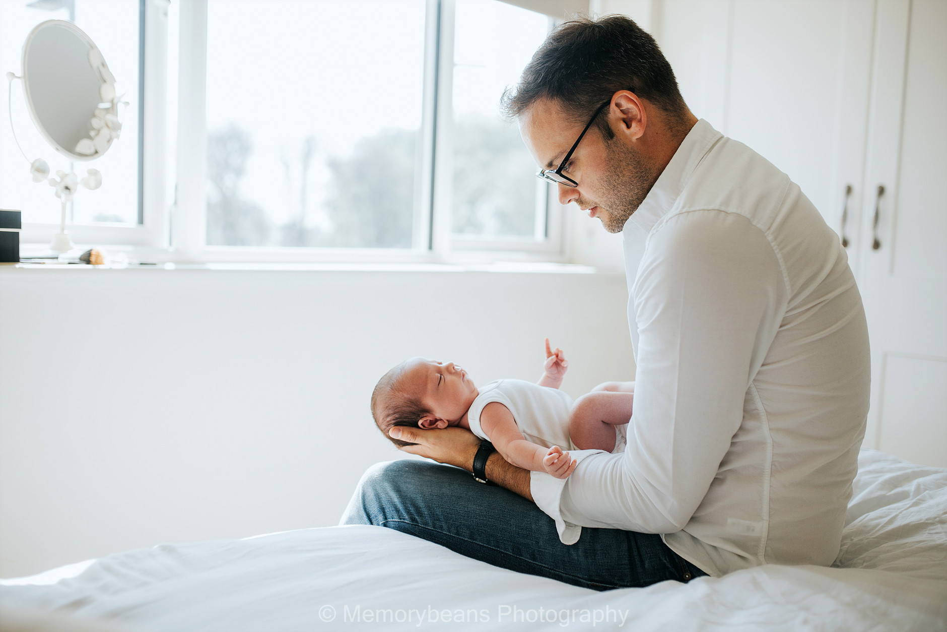 Father sitting on the bed holding and looking at his baby