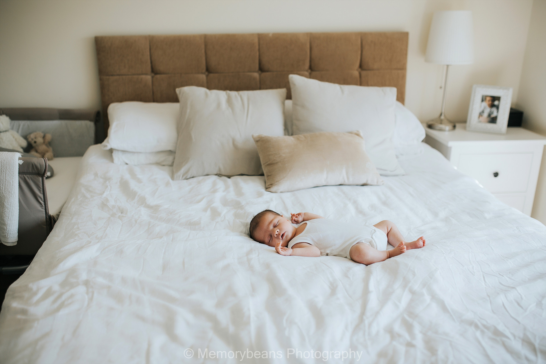 Newborn sleeping baby on his own on his big parents bed