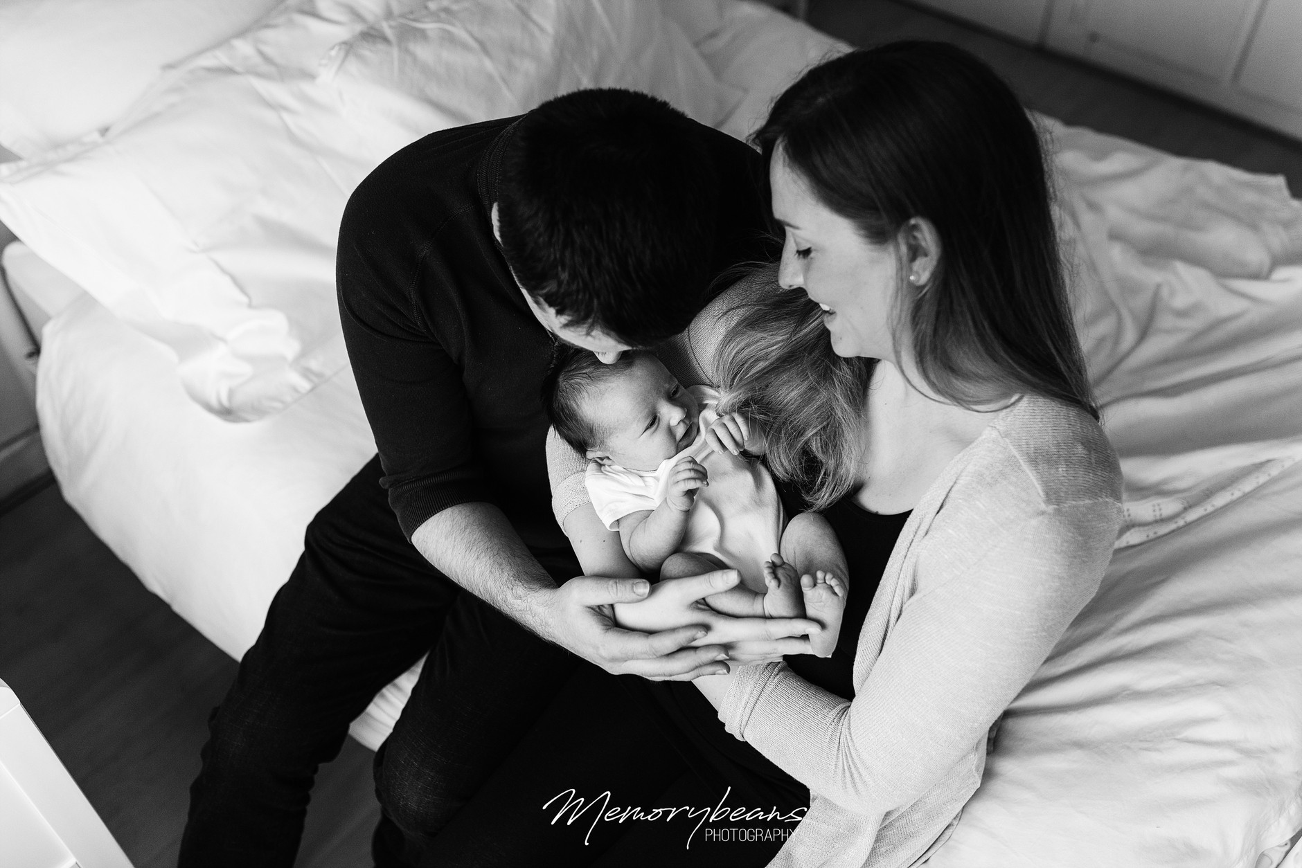 Black & White Photograph of new parents holding smiling baby at home