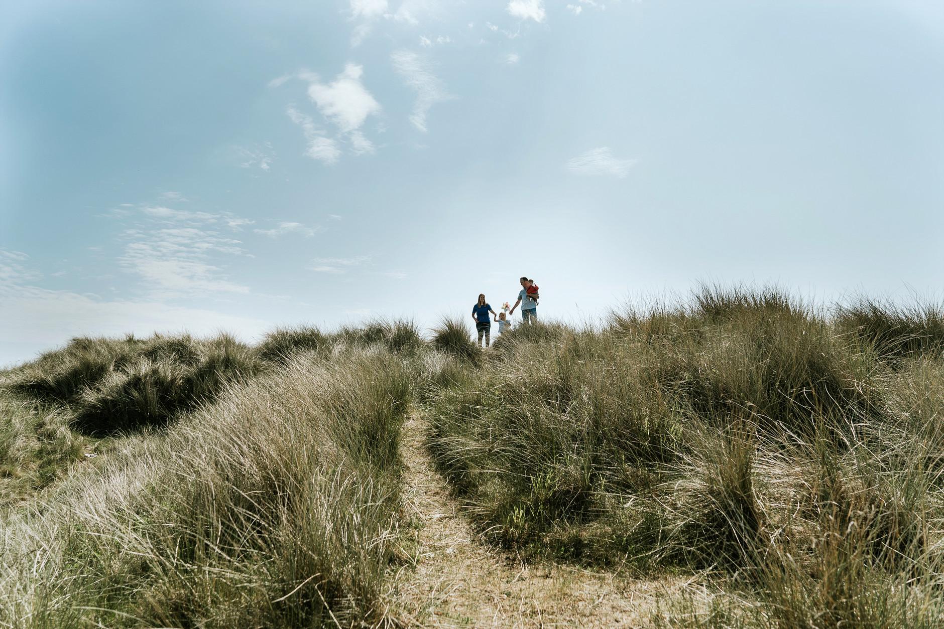 Family of four walking in the sand dunes in Bull Island, Dublin