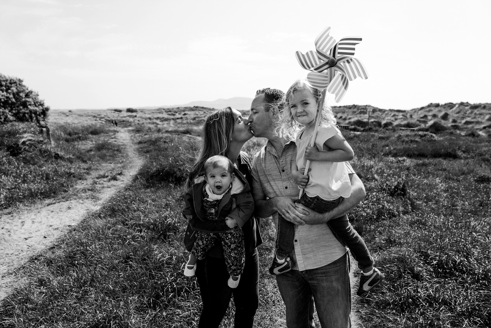 Parents kissing and holding their two girls during their vacation photoshoot in Dublin