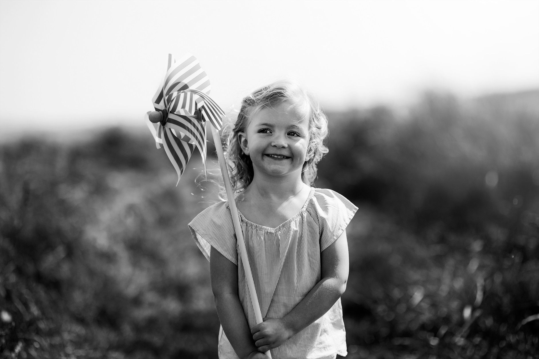 Little girl smiling and holding a wind mill in the sand dunes