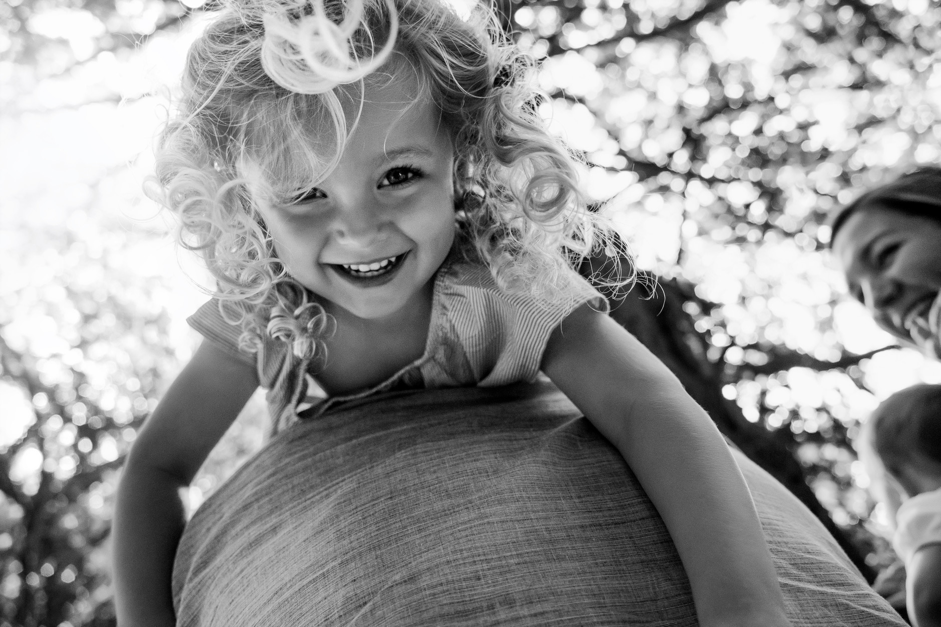 Little girl with blond curly hair laughing and hanging upside down on her father's shoulder
