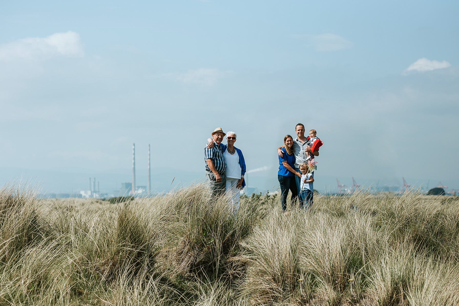 Three generations of one family posing for a family portrait in Bull Island sand dunes in Dublin: grandparents, parents and two granddaughters.