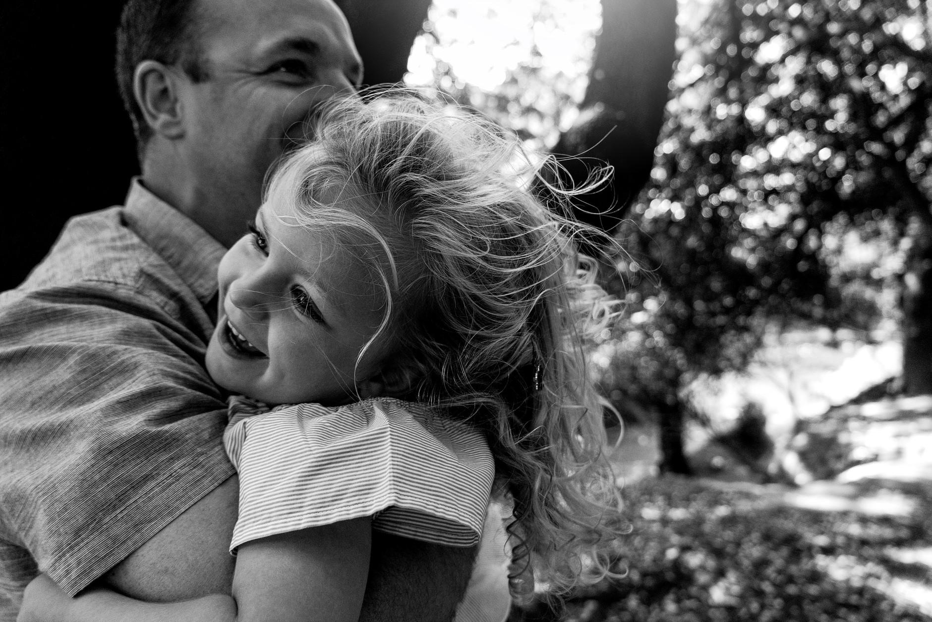 Dad hugging his laughing daughter