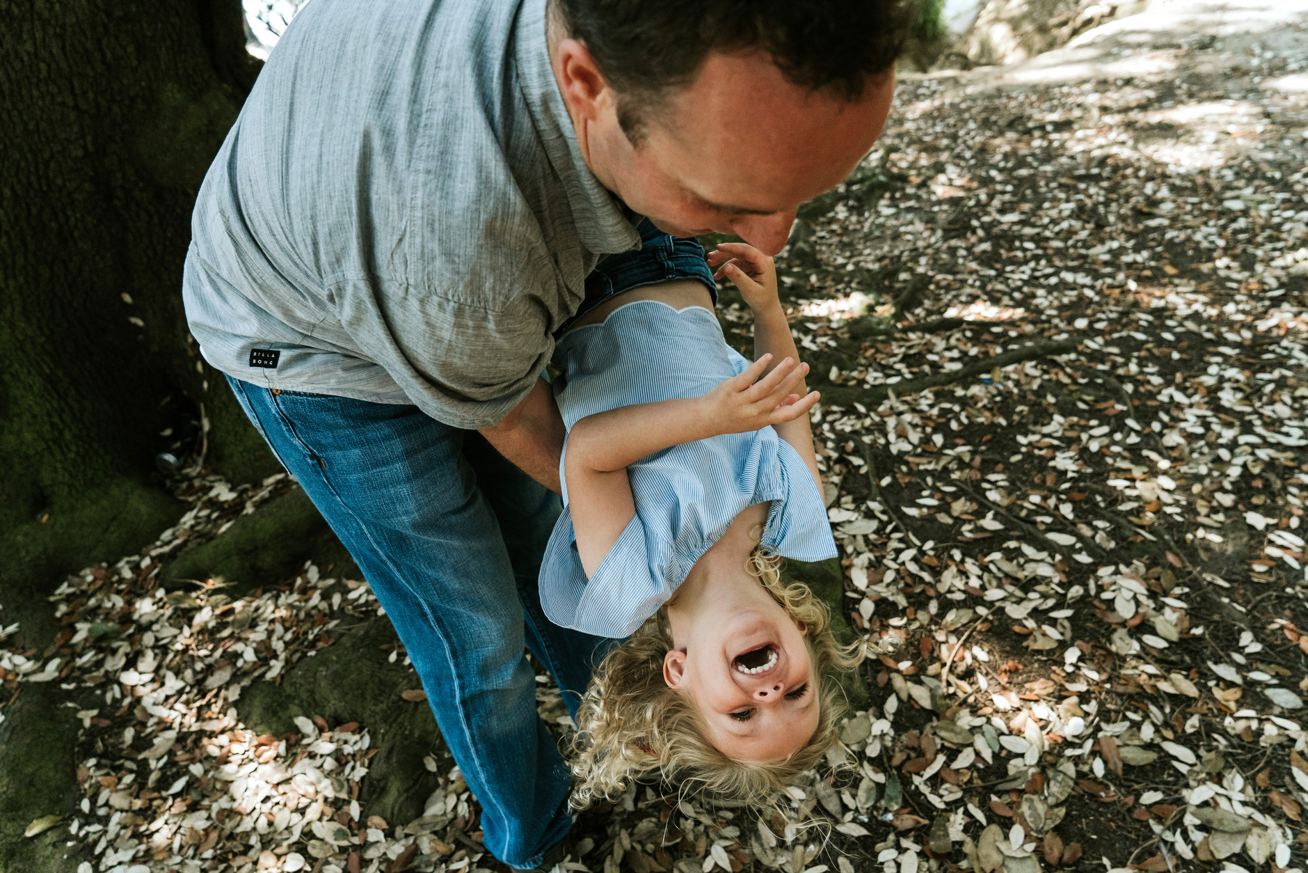 Little girl laughing while her dad swings her upside down: fun