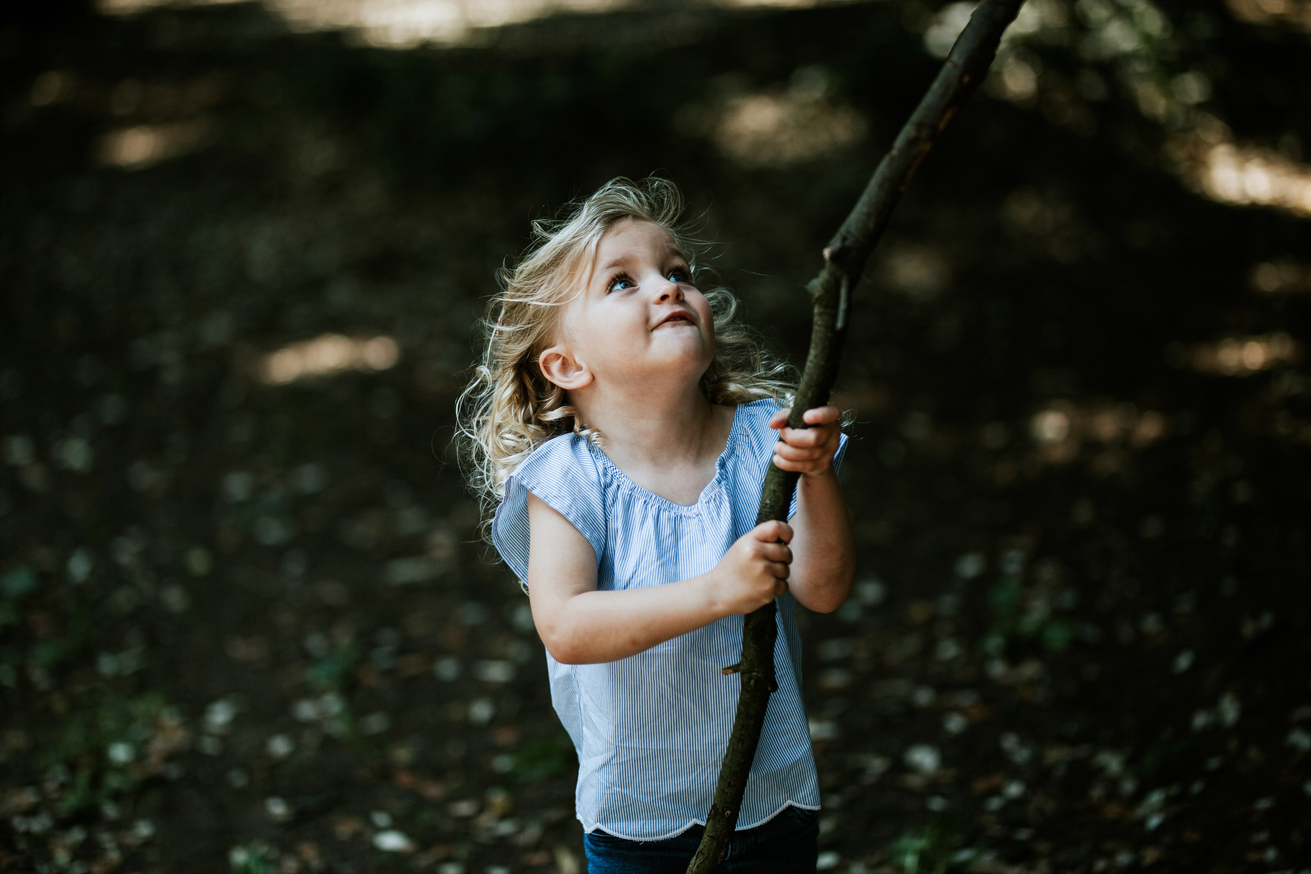 Little blond curly girl playing with a big stick in the park on their vacation in Dublin
