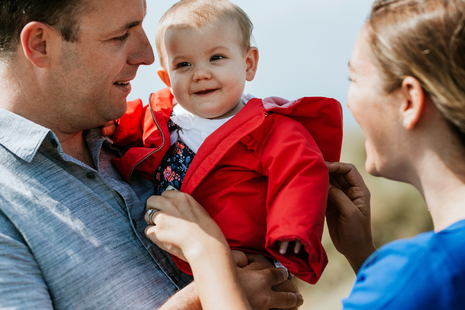 Little baby girl in red coat in her father's arms and mother smiling