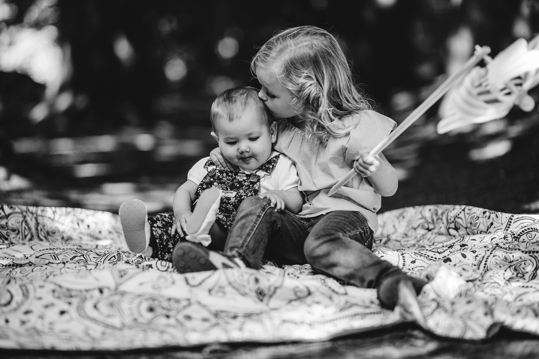 Big sister kissing baby on the head on a blanket in a park
