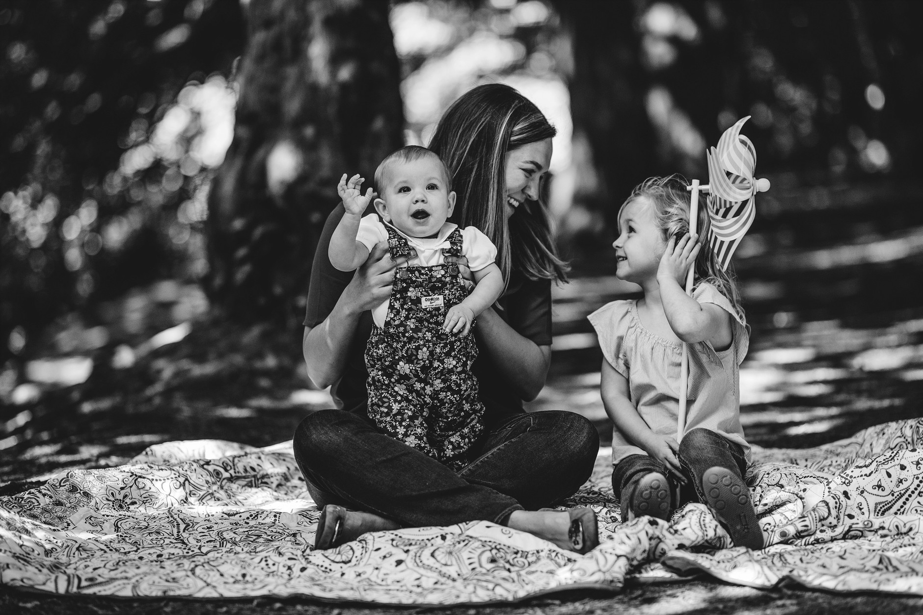 Mother and her two daughters sitting on the blanket and laughing