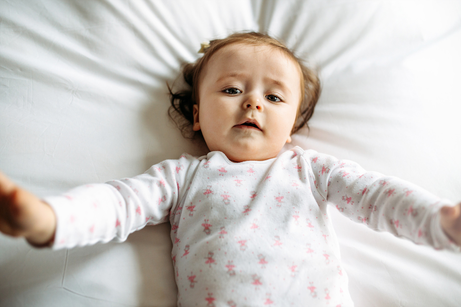 One-Year-Old baby lying on a bed and looking at the camera