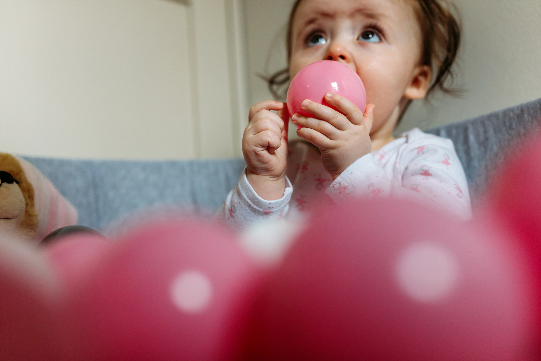 Close up of baby girl licking a pink ball from the ball pool