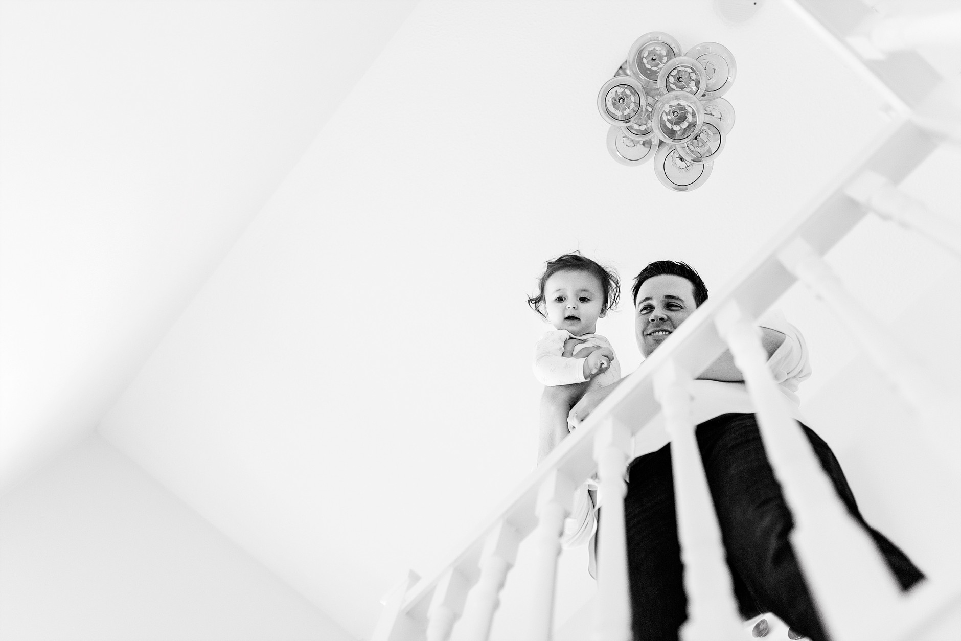 Looking up at baby and father at the top of the stairs