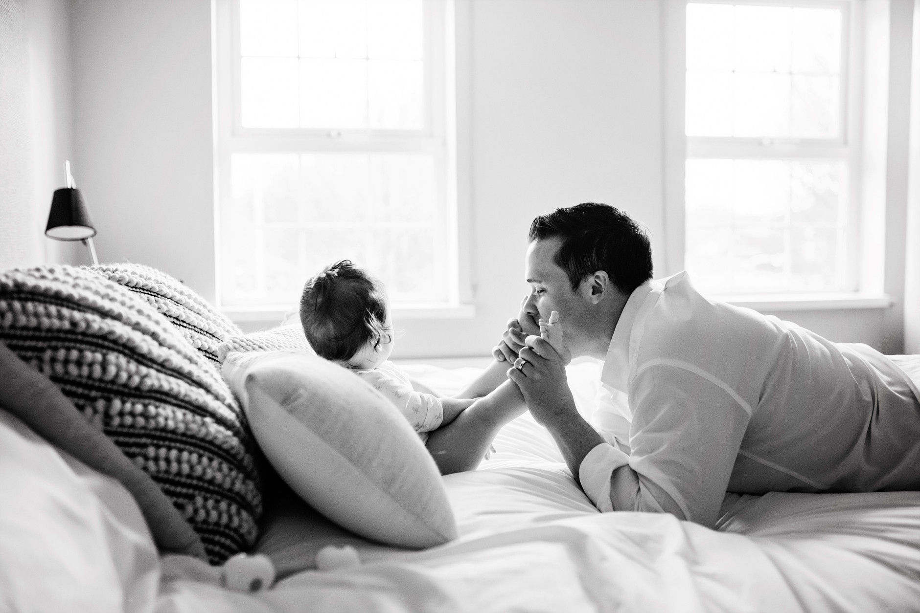 Father playing and kissing his daughter's feet on the bed
